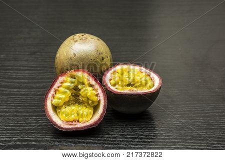 Split ripe fruit of Passiflora edulis on dark wood.