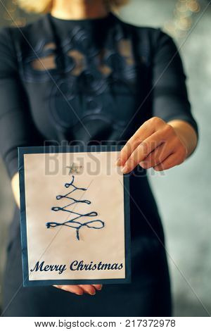 Girl holding a christmas tree card in front of her face covered selected focus on the card and hands Christmas concept