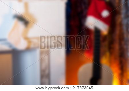 Abstract Christmas blurred background, an acoustic guitar in a Santa hat and a white fireplace with stocking