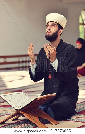 Muslim man and woman praying for Allah in the mosque together.