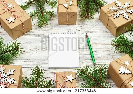 Christmas to-do list or wish list. Christmas background with blank notebook fir branches decorations and gift boxes. Copy space. Top view.