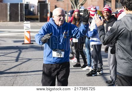 West Islip NY USA - 24 November 2017: A runner receives high fives from the school track team as he approaches the end of the annual Run Your Turkey Off 4K turkey trot.