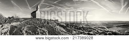 Romanesque church Saint Michael Drazovce village and industrial park Nitra - North in sunset Slovak republic. Black and white photo. Landscape in middle Europe.