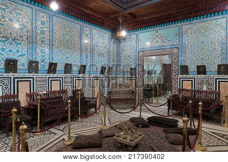 Cairo Egypt - December 2 2017: Manial Palace of Prince Mohammed Ali. The mirrors room at the residence building with Turkish floral blue pattern ceramic tiles wall and decorated wooden ceiling