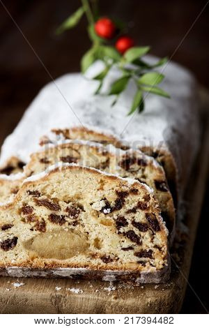 closeup of a stollen cake for christmas time sprinkled with icing sugar, placed on a wooden rustic table