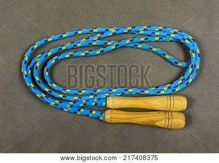 Blue skipping rope on a textile background.