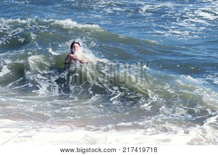The girl is knocked off waves by the sea