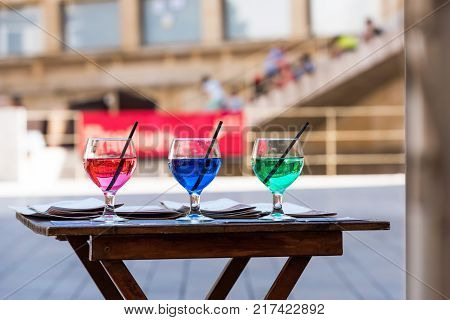 Three Glasses With Colorful Cocktails Near The Cafe, Siurana, Catalunya, Spain. Copy Space For Text.