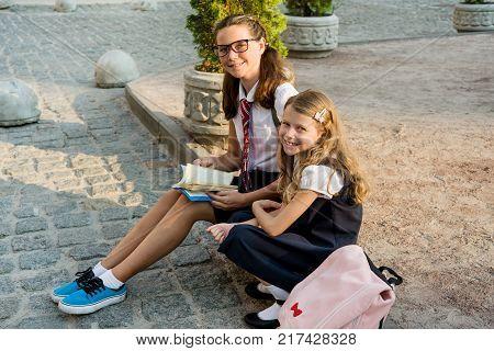 Schoolchildren reading a book sitting on the sidewalk.