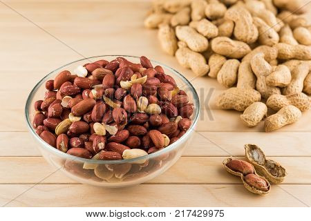 Glass bowl full of peeled peanuts and peanuts in nutshell on a wooden table