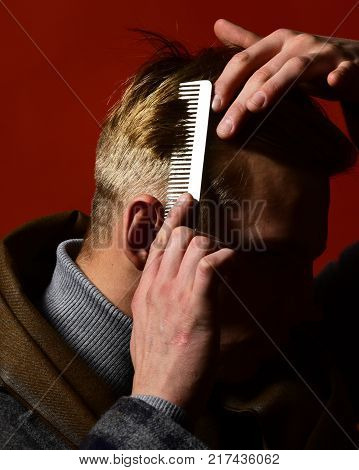Stylist combing his hair on red background. Man in vintage style holds white comb. Guy in suit and scarf with healthy hair. Hairdressers and style concept.