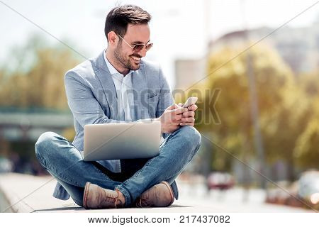 Attractive man sitting outside on concrete using mobile phone and laptop looking down while sitting with legs crossed