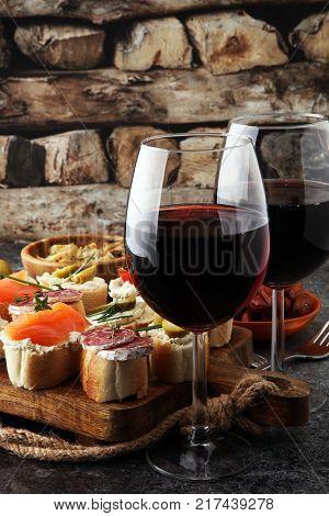 Italian antipasti wine snacks set. Cheese variety Mediterranean olives pickles salami salmon tomatoes artichokes and wine in glasses. Spanish tapas