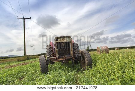 Old abandoned Tractor in Field with telegraph poles and hay bales.