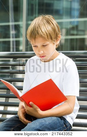 Child flipping through book pages outdoors in the city