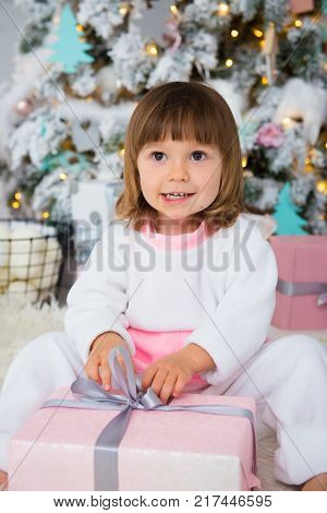 Funny baby girl in white and pink fleece pajamas sitting near Christmas tree and unpacking New Year gift.
