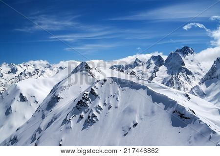Winter mountains with snow cornice and beautiful blue sky with clouds in cold sun day. Caucasus Mountains region Dombay. View from top of Mount Musa Achitara. poster