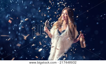 Well-dressed pretty woman in fur coat drinking champagne and standing in falling confetti with snow.