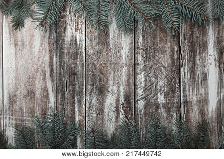 Old wooden background. Green fir branches at the top and bottom. Space for congratulation message of Xmas, Christmas and New Year. Rustic. Xmas and Happy New Year composition. Flat lay, top view