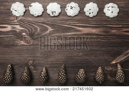Brown wood background with pronounced texture. With golden cones and sweet biscuits arranged diametrically opposed. Space for a greeting message. Top View.