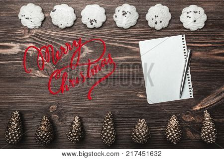 Brown wood background. Gold cones and sweet biscuits arranged diametrically opposed. Letter and space for a greeting message. Top View. With Christmas.
