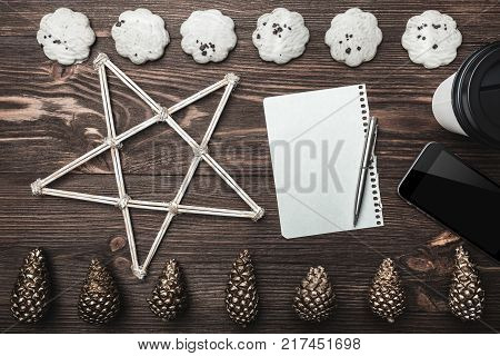 Brown wood background. Gold cones and sweet biscuits arranged diametrically opposed. Letter, phone, star and coffee, space for a greeting message. Top View.