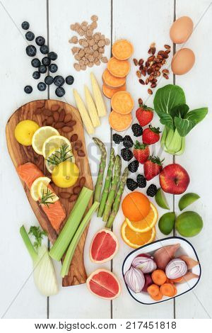 Health food for dieting concept with fresh salmon, fruit, vegetables, dairy, nuts and cereals.  Super foods high in  anthocyanins, antioxidants, fiber and vitamins. Top view on rustic wood background.