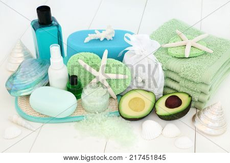 Skincare and body care spa beauty treatment with avocado, bath salts, sponges, face cloths, tea tree aromatherapy essential oil, body lotion, bath foam, soap and decorative shells on white wood.