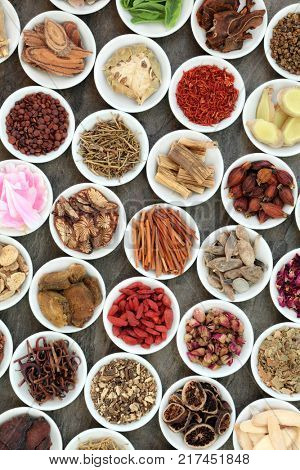 Chinese alternative medicine with traditional herbs in white porcelain bowls on marble background. Top view.