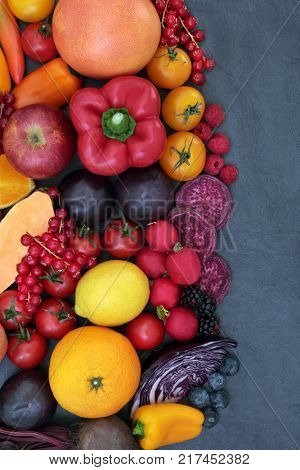 Healthy super food background border with fruit and vegetable selection on slate, high in antioxidants, anthocyanins and vitamins. Health promoting concept, top view.