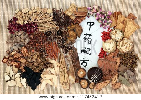 Chinese alternative herbal medicine with acupuncture needles, herbs and calligraphy script on rice paper on bamboo background. Translation reads as chinese alternative medicine. Top view.