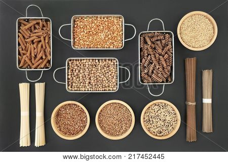Dried macrobiotic health food with udon and soba noodles, grains, legumes, seeds and whole wheat pasta. Foods high in smart carbohydrates, protein, antioxidants and fiber, top view.