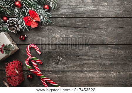 Christmas greeting card on wood background, fir branches, cone, message space, toys, colorful candies and xmas gifts. Top view.