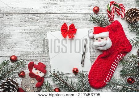 Christmas sock with presents. Christmas decoration stocking and toys hanging over gray rustic wooden background. The socks of burlap Christmas sweets, gifts, cakes. Christmas snowflakes. Top view