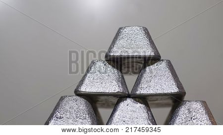 Tin metal ingots / bullion in pyramid formation with grey background