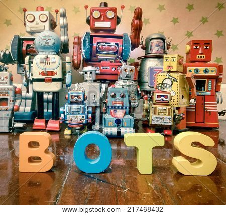 the word BOTS with wooden letters on wooden floor with retro robot toys
