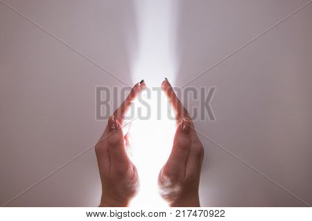 Hands reaching out to holy light. Miracle faith in God and religion concept