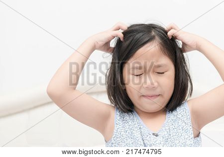kid with freckles scratching his hair for head lice or allergies Health care concept