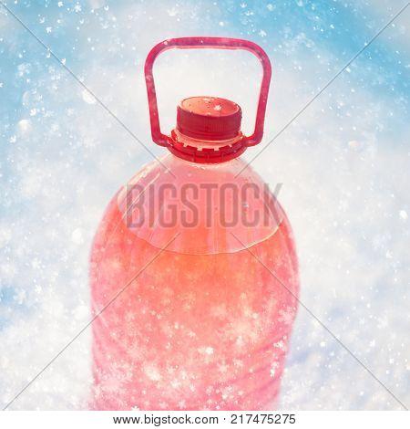 bottle with non-freezing windshield washer fluid, snowflakes background