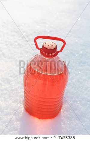 bottle with non-freezing windshield washer fluid, snow background