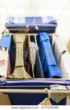 Many colorful clothing on drying rack clothes horse after laundry. Clean home interior concept.