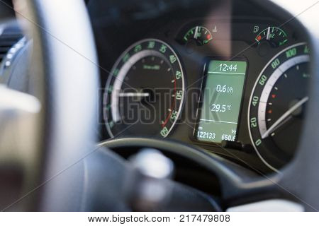 Close up dashboard of a modern car mileage and temperature.