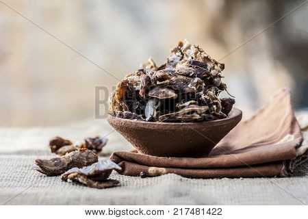 Raw Tamarindus indica,tamarind in a clay bowl on gunny background.
