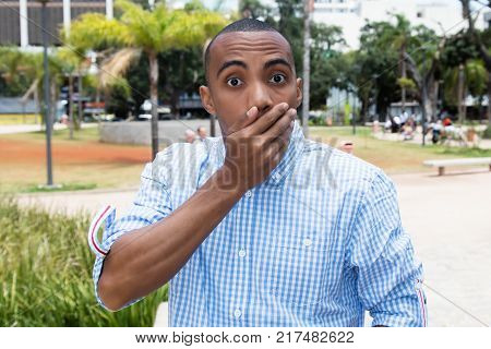 Shocked african american man outdoors in the summer in the city
