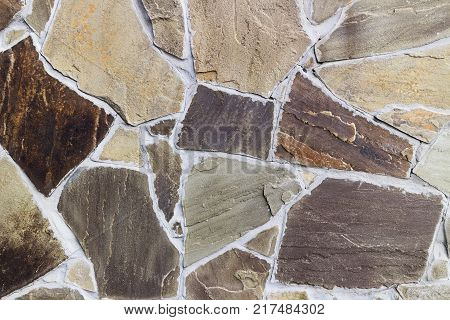Wall with irregularly shaped brown and beige tiles.