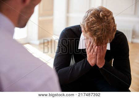 School Counselor Talking To Depressed Male Pupil