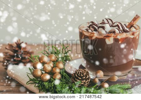 Hot chocolate in glass topping with marshmallow and chocolate sauce. Homemade hot chocolate or cacoa on wood table side view copy space in Christmas theme and snowfall background. Concept of Christmas drink. Delicious hot chocolate for Christmas party.