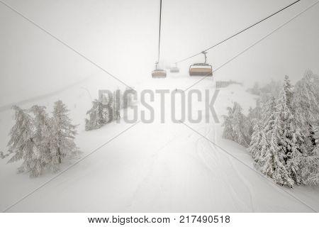 Ski lift in fog and snowfall on ski resort