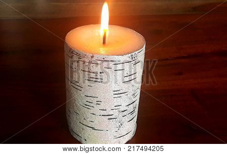 candle with a burning wick decorated with white birch bark