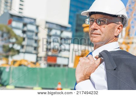 Confident construction engineer in hardhat and with jacket on shoulder